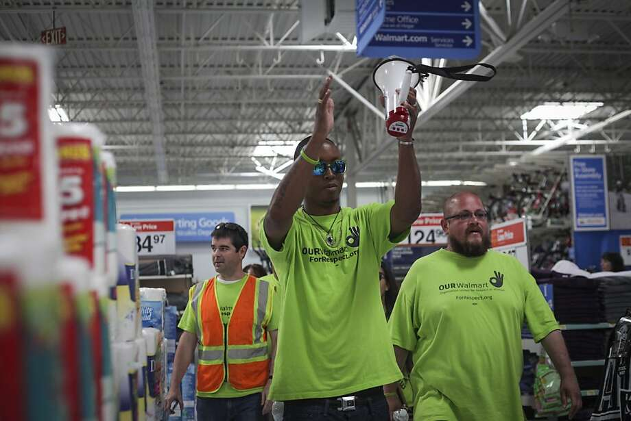 Former employees Dominic Ware (center) and Raymond Bravo lead protesters through an Oakland Walmart store Thursday. Steven Owirka (left), is from Organization United for Respect at Walmart, which mobilizes workers and their supporters. Photo: Sam Wolson, Special To The Chronicle