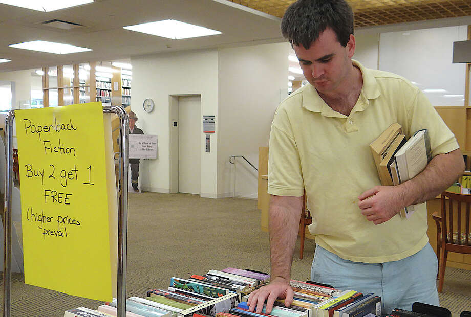 Andrew Baumgardner of Fairfield bowses through the books in the adult paperback fiction section of the Fairfield Public Library's Back to School Book Sale. Photo: Mike Lauterborn / Fairfield Citizen contributed