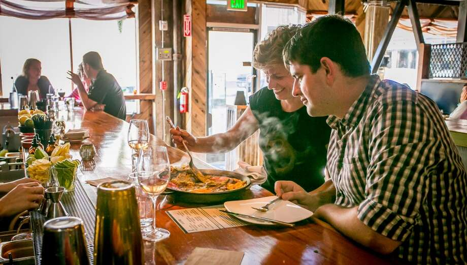 A couple enjoys Paella at the bar at Duende in Oakland. Photo: John Storey, Special To The Chronicle