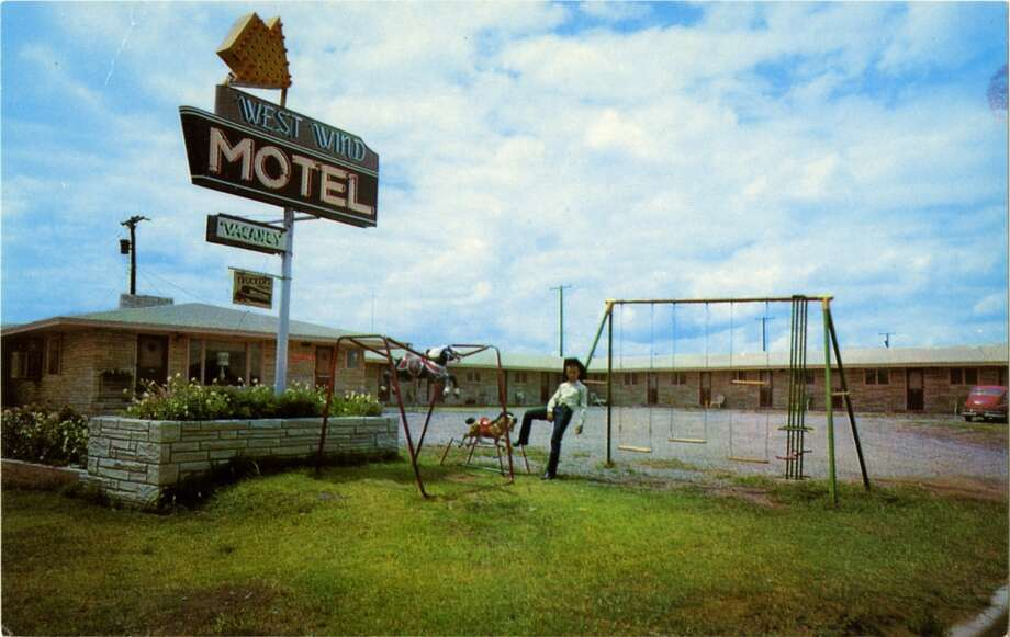 Postcard view of the exterior of the West Wind Motel showing the one story brick structure, the large neon sign, and a small pay area.  (Photo by Lake County Museum/Getty Images) Photo: Getty Images