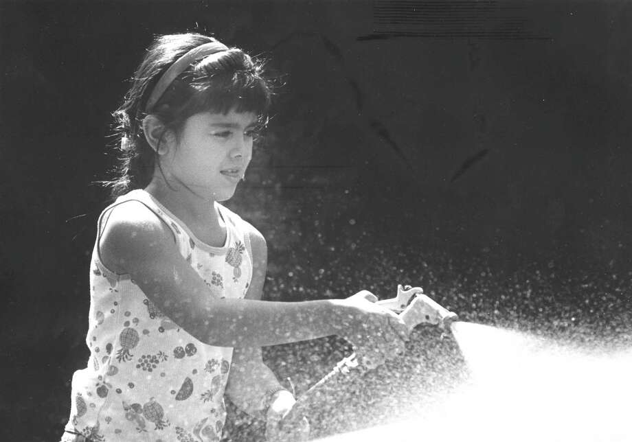 Clarissa Montalvo, 6, of Stamford, helps wash her mother's car while visiting her grandmother's home on Hope Street on Sept. 1, 1988. Photo: Advocate
