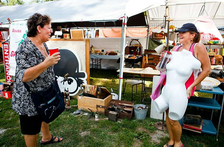 Oh, it's you! Lori Knight tries on a torso for her cousin, Debbie Graham, at the Sparks, Kan., Antiques and Collectibles Flea Market. Photo: Sait Serkan Gurbuz, Associated Press
