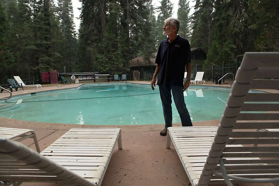 "Steven Bloxham, who operates the Pinecrest Chalet in Tuolumne County with his wife, Gail, walks through the deserted pool area on Tuesday. ""It's just so weird for it to be empty at this time of year,"" he says. Photo: Michael Macor, San Francisco Chronicle"