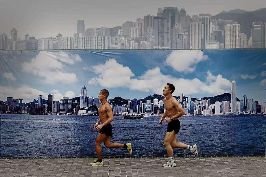 "The famous wrinkled sky of Hong Kong: So that visitors can pose for photos in front of Hong Kong's ""beautiful skyline,"" the city has thoughtfully erected a billboard that shows the waterfront on a clear day, which almost never happens. Apparently tourists find it more appealing than the real thing. Photo: Philippe Lopez, AFP/Getty Images"