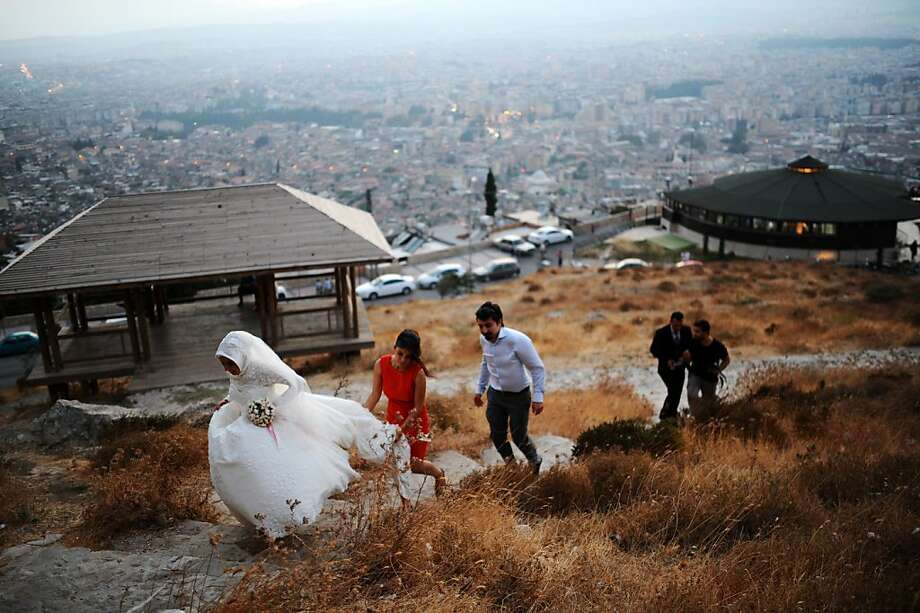 It's all downhill after this: A newly married couple hike up a hill above the city of Antakia, Turkey. Photo: Bulent Kilic, AFP/Getty Images