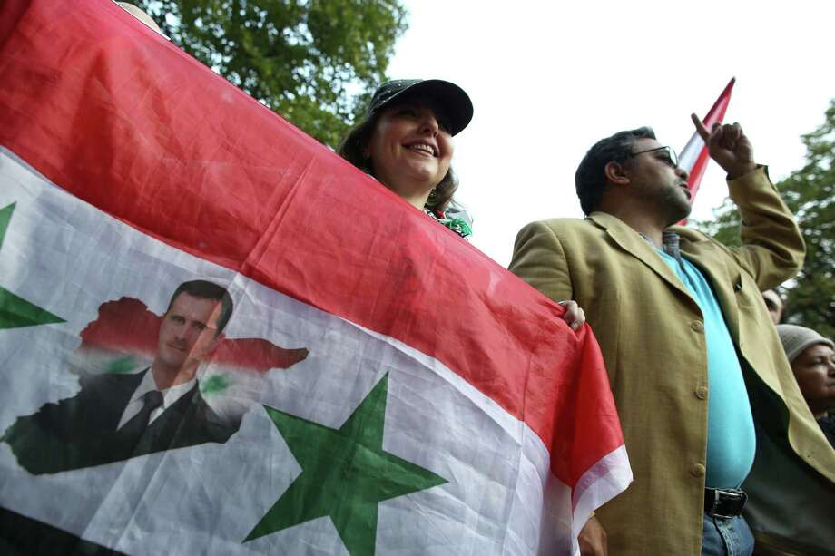 A pro-Assad regime demonstrator holds a sign and a national flag as she demonstrates against French and foreign military involvement in Syria in Paris on Thursday. Photo: Kenzo Tribouillard / Getty Images