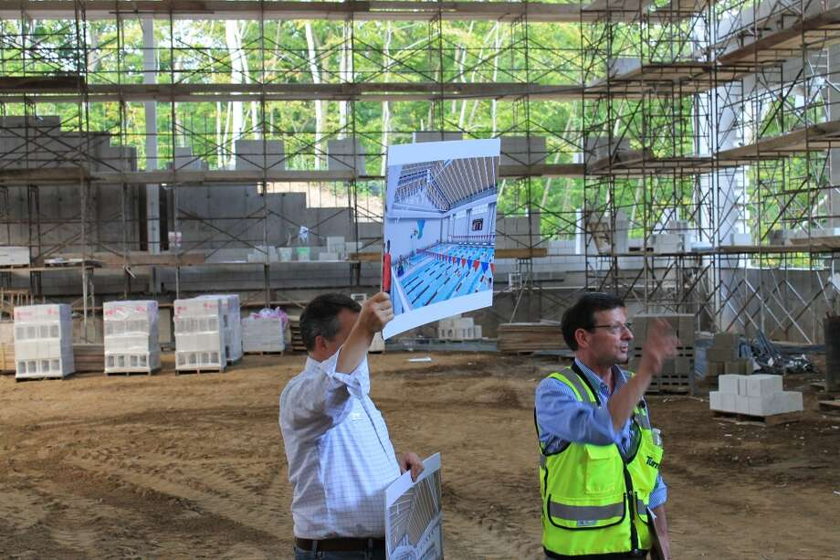 Development Officer Paul Berntesky holds up a rendering of the Aquatic Center.