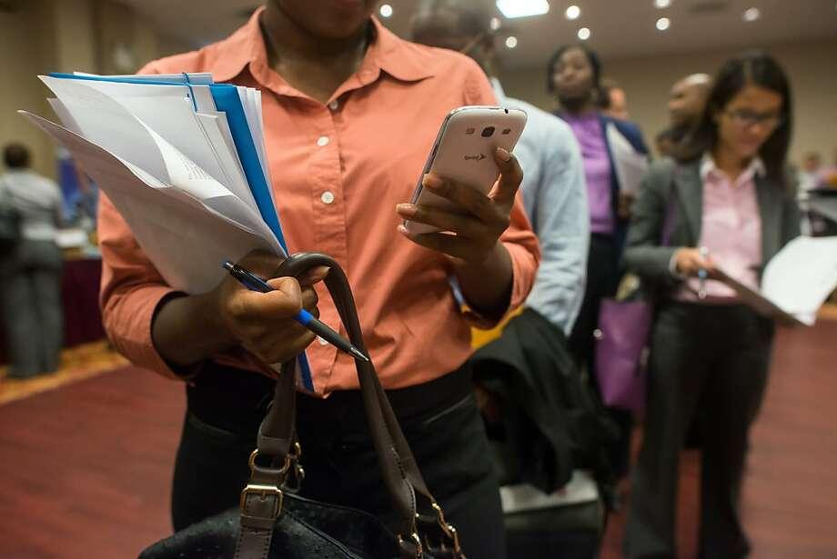 Job seeker Shalana Roberts (left) waits in line at a New York job fair. Photo: Craig Warga, Bloomberg