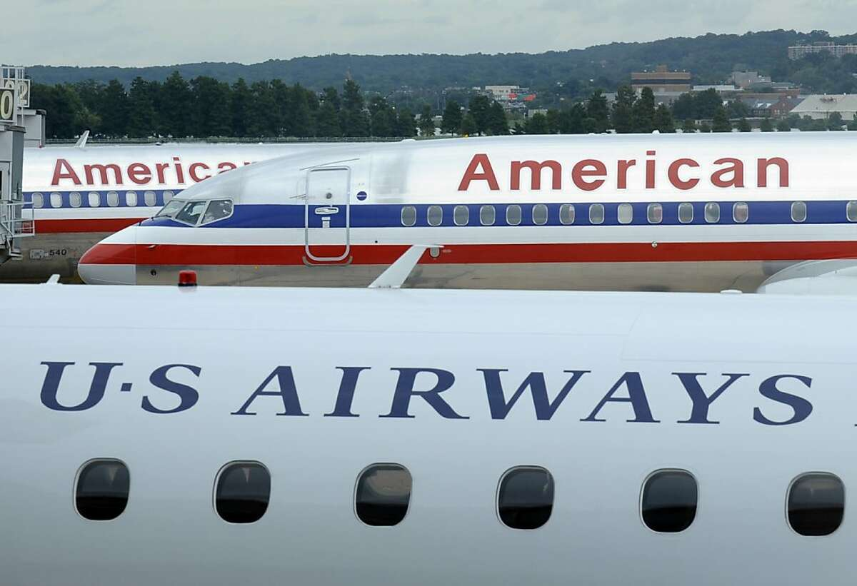 American Airlines planes and a US Airways plane at parked at Washington's Reagan National Airport, Tuesday, Aug. 13, 2013. The Justice Department and a number of U.S. state attorneys general on Tuesday challenged a proposed $11 billion merger between US Airways Group Inc. and American Airlines' parent company, AMR Corp.(AP Photo/Susan Walsh)