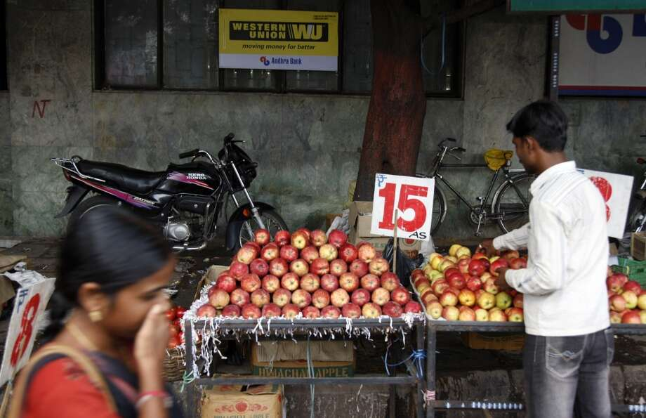 India: A vendor arranges fruits on his cart while on a street in Hyderabad, India. Photo: Mahesh Kumar A., Associated Press