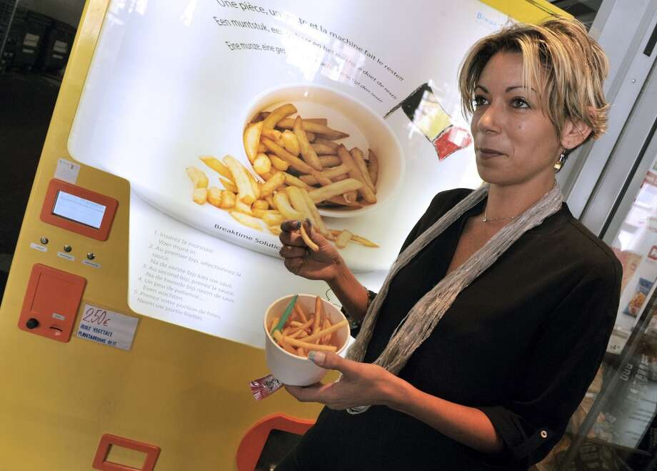 Belgium: Tuline Bey, director of the company that manufactured the first fries vending machine installed in Brussels on August 29 explains the operation of this fries machine. The portion of 135 grams of chips costs 2.50 Euros, including sauce. The cooking takes a minute and a half. The machine is also equipped with a remote management system which informs the user via SMS on stock status. Photo: Gorges Gobet, AFP/Getty Images