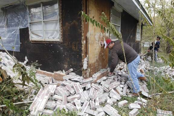 Chad Devereaux examines bricks that fell from three sides of his in-laws home in Sparks, Okla. on Sunday, Nov. 6, 2011 after two earthquakes hit the area in less than 24 hours. A team of scientists determined that a 5.6 magnitude quake in Oklahoma in 2011 was caused when oil drilling waste was injected deep underground. The report was released Tuesday, March 26, 2013 by the journal Geology. That makes it the most powerful quake to be blamed on deep injections of wastewater, although not everyone agrees. Oklahoma's state seismologists say the quake was natural.