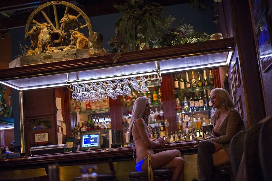 Jaylynn Jones (left) and Sarah Vandella sit at the bar at Mustang Ranch in Sparks, Nev. The brothel has seen business decline with the economy, particularly from truckers squeezed by rising fuel costs, and as more people arrange liaisons through the Internet. Photo: David Paul Morris, Bloomberg