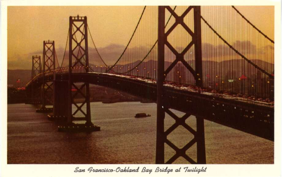 A 1957 vintage postcard showing the San Francisco-Oakland Bay Bridge aglow with twinkling lights as it crosses the bay, the city and mountains visible in the distance. Photo: Curt Teich Postcard Archives, Getty Images
