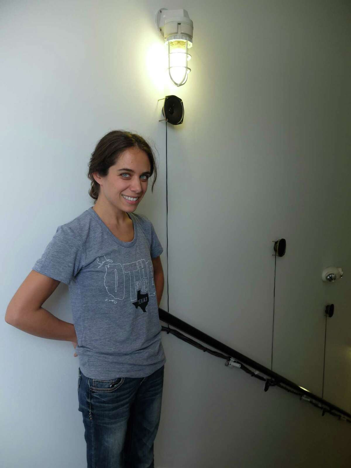 """Multi-media artist Lina Dib in a stairwell at Lawndale Art Center, where she's placed speakers that emit motion-activated sounds for the installation """"Murmurations."""""""