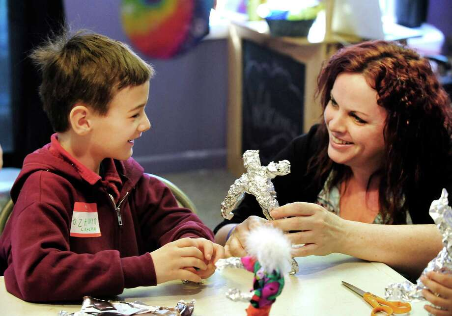 "Wendy Mitchell helps Zach Catalano, 6, during a program titled "" Home and Commyounity"" at the Sandy Hook Arts Center for Kids. Mitchell was a Sandy Hook fifth grader in 1980 and she clearly remembers that the class had buried a time capsule at the school. Photo: Michael Duffy / The News-Times"