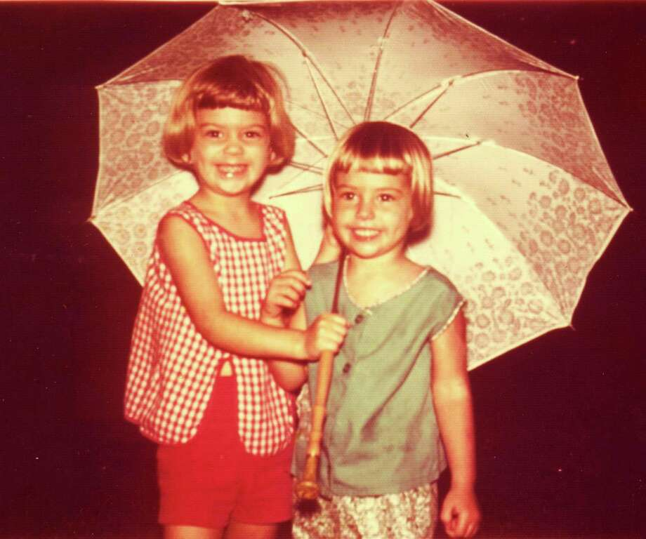 Then: In 1968 the Semlinger sisters, Mary Ann, 5, and Caroline, 4, were captured huddled under an umbrella in the rain outside their San Antonio home. Photo: Semlinger, Reader Submission