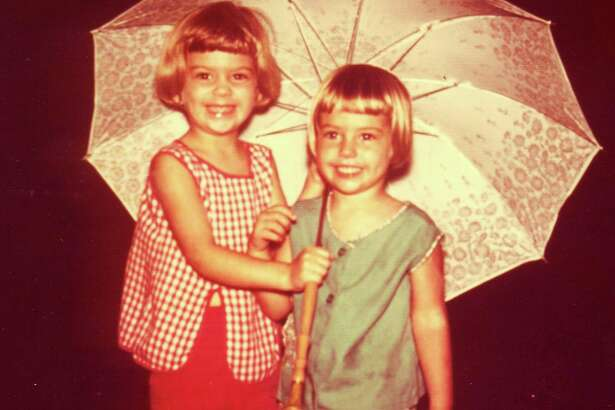 In 1968 the Semlinger sisters, Mary Ann, 5, and Caroline, 4, were captured huddled under an umbrella in the rain outside their San Antonio home.