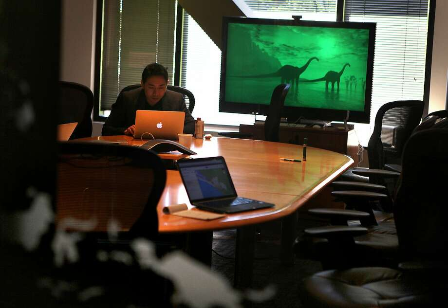 Julian Wong works on his computer in the main conference room of oDesk in Redwood City in 2013. Photo: Liz Hafalia, The Chronicle