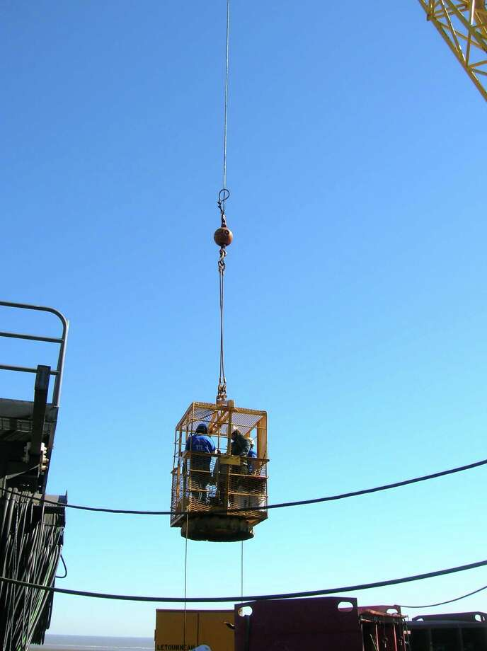 A crane hoists Zadok Technologies engineers at a work site where they're doing an installation. Photo: Zadok Technologies