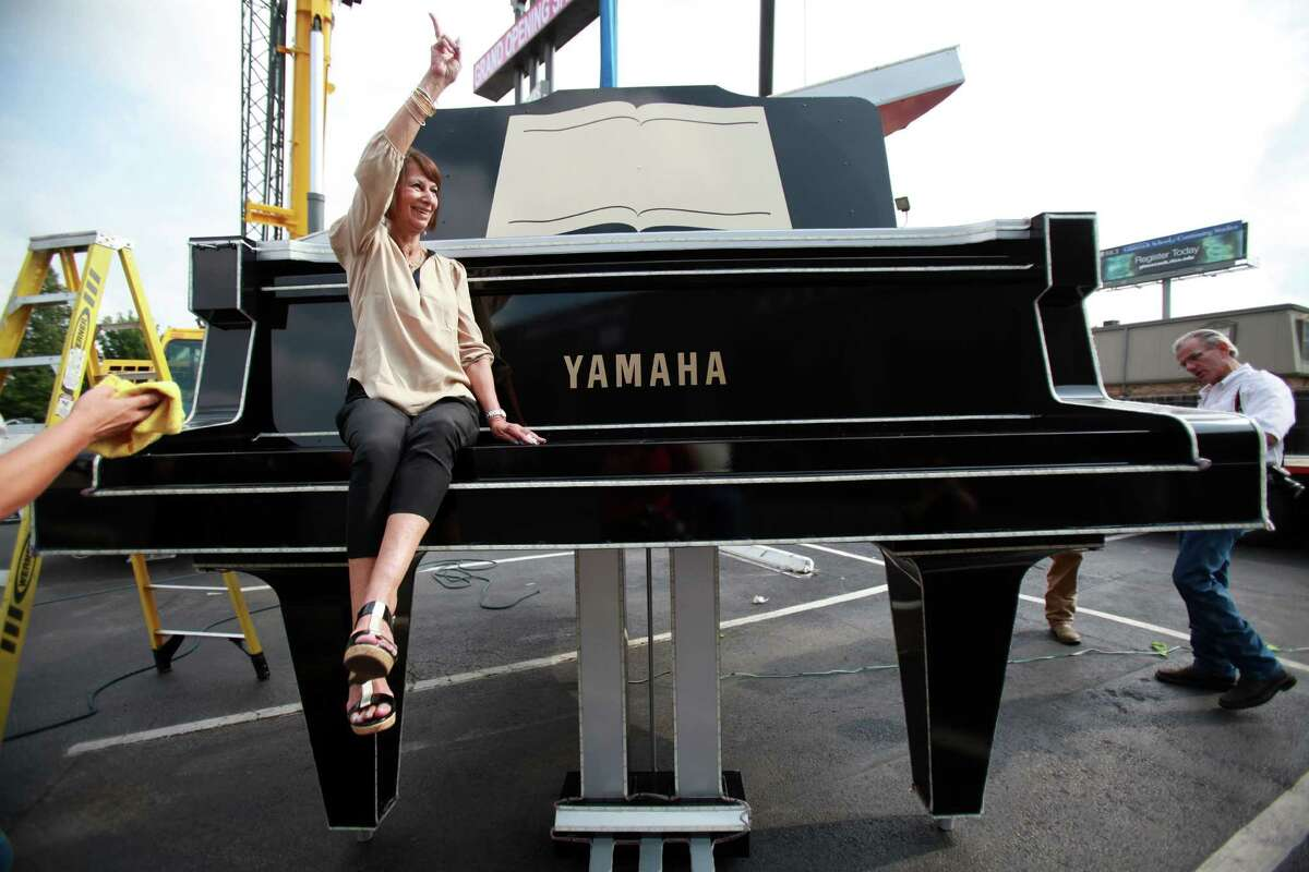 Long time employee Evie Offord, Marketing Manager at Fort Bend Music Center, waves to staff members after taking a photo with the restored oversized Yamaha piano on Friday, Aug. 30, 2013, in Houston. Sparkles sign company lifted the piano on to a 110 foot sign along Buffalo Speedway and Highway 59.