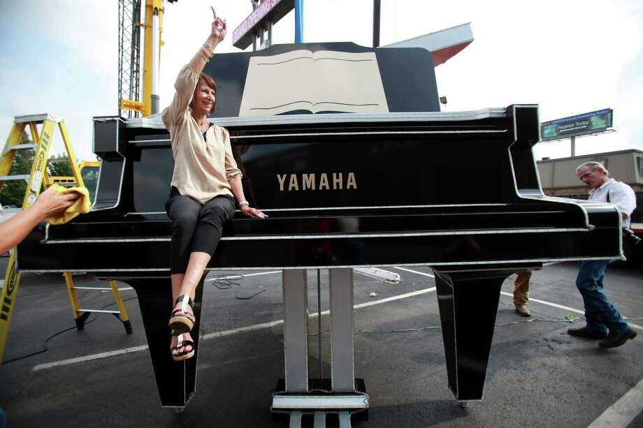 Long time employee Evie Offord, Marketing Manager at Fort Bend Music Center, waves to staff members after taking a photo with the restored oversized Yamaha piano on Friday, Aug. 30, 2013, in Houston. Sparkles sign company lifted the piano on to a 110 foot sign along Buffalo Speedway and Highway 59. Photo: Mayra Beltran, Houston Chronicle / © 2013 Houston Chronicle