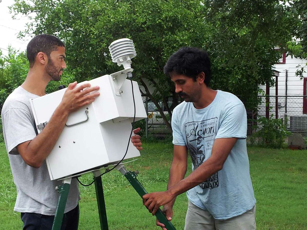 Troy Sanders and Sparsh Khandeshi erect an air monitor to sense contaminants in the community of Manchester near the Houston Ship Channel.