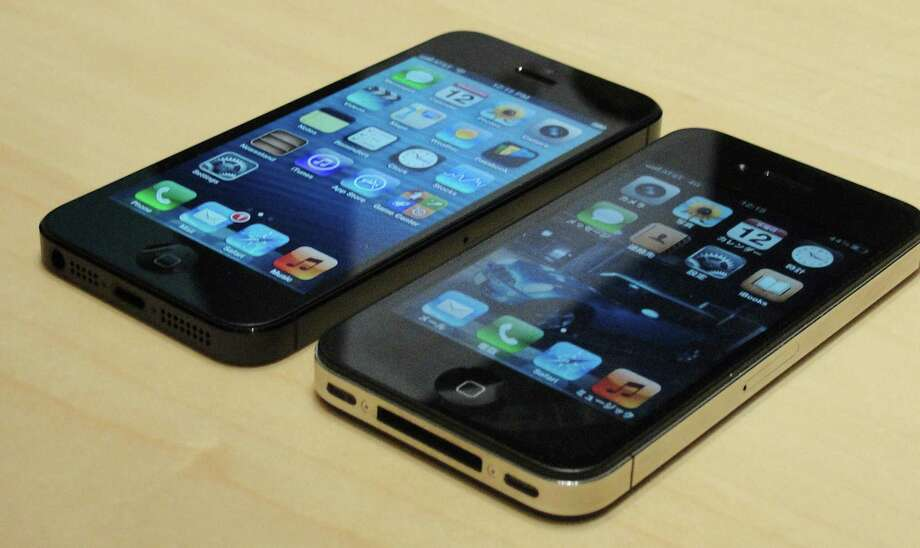 Apple's iPhone 5 (left) and previous-generation 4S. U.S. owners of iPhones can trade in their devices for credit toward newer models. Photo: Glenn Chapman / Getty Images