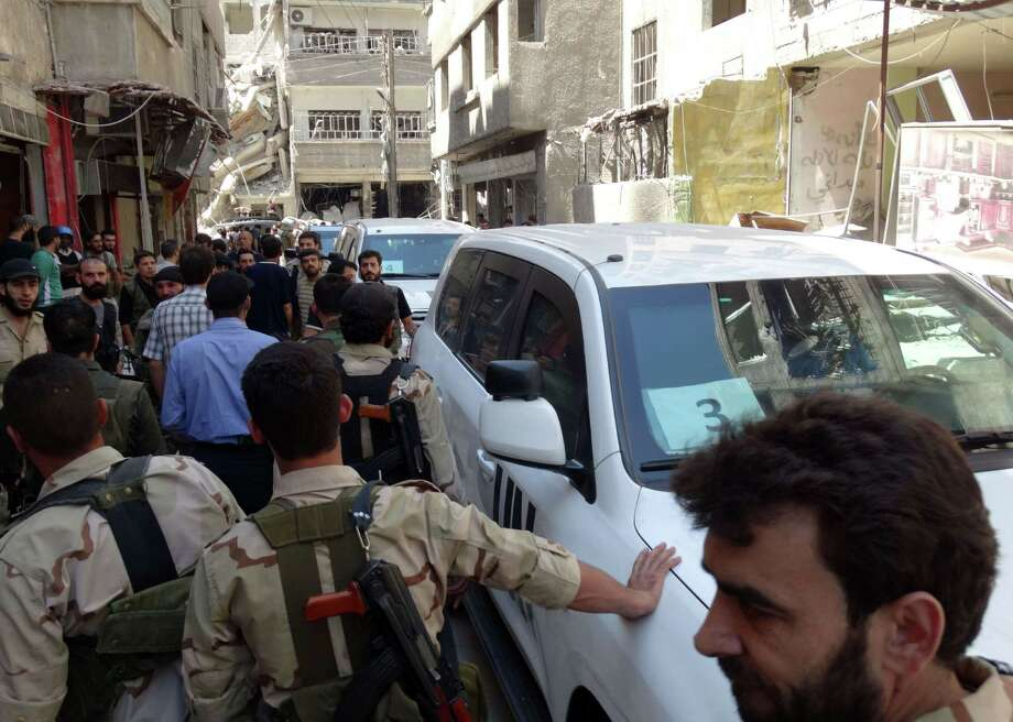 Syrian rebel fighters and civilians surrounded the U.N. arms experts as they  arrived last week to inspect a possible chemical attack site outside Damascus. Photo: MOHAMED ABDULLAH, Stringer / AFP
