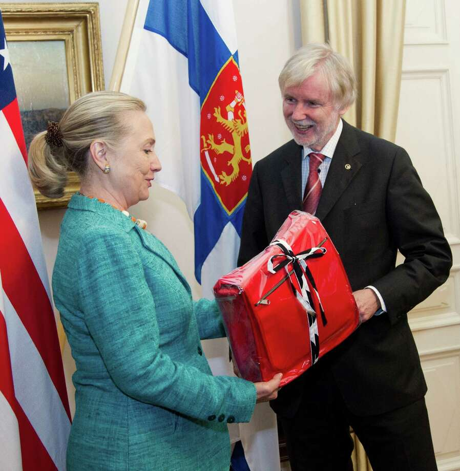 Then-Secretary of State Hillary Rodham Clinton receives a gift from Finnish Foreign Minister Erkki Tuomioja in Helsinki, Finland, on June 2012. Photo: Haraz N. Ghanbari, POOL / AP