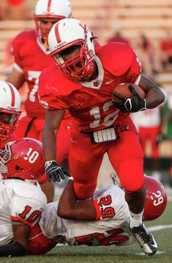 Bellaire running back Reshard Waddel (12) is tackled from behind during the first quarter of a high school football game at Butler Stadium on Friday, Aug. 30, 2013, in Houston, Texas. Photo: Andrew Richardson, For The Chronicle / © 2013 Andrew Richardson
