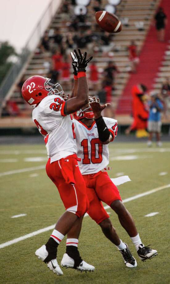Alief-Taylor running back Steven Thompson (22) collides with safety Josh Kalu (10) while attempting to field a kick during the second quarter of a high school football game at Butler Stadium on Friday, Aug. 30, 2013, in Houston, Texas. Photo: Andrew Richardson, For The Chronicle / © 2013 Andrew Richardson