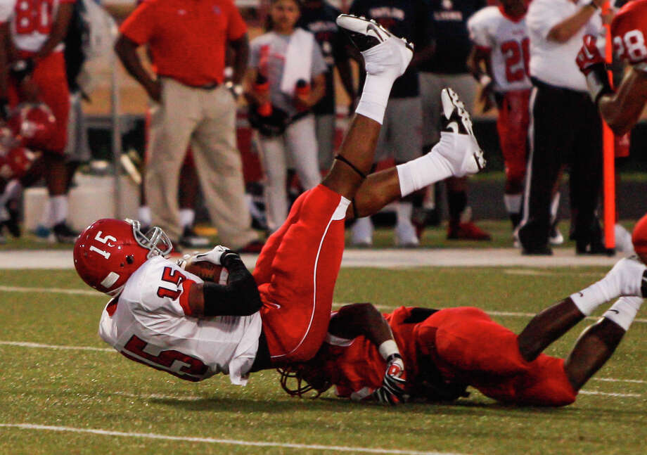 Alief-Taylor wide receiver Romello Brooker (15) has his legs taken out from under him during the second quarter of a high school football game at Butler Stadium on Friday, Aug. 30, 2013, in Houston, Texas. Photo: Andrew Richardson, For The Chronicle / © 2013 Andrew Richardson