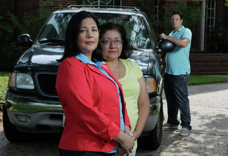 Yvonne Scherz, left, her sister Irma Montes and son David Scherz pose in front of their home where five family members were arrested by deputy constables. All charges against the family were dropped, and they have filed a civil rights suit. Photo: Scherz Family, Staff / © 2013  Houston Chronicle