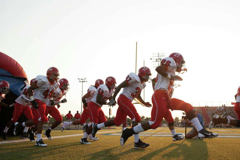 The Alief-Taylor Lions run onto the field prior to the first quarter of a high school football game at Butler Stadium on Friday, Aug. 30, 2013, in Houston, Texas. Photo: Andrew Richardson, For The Chronicle / © 2013 Andrew Richardson