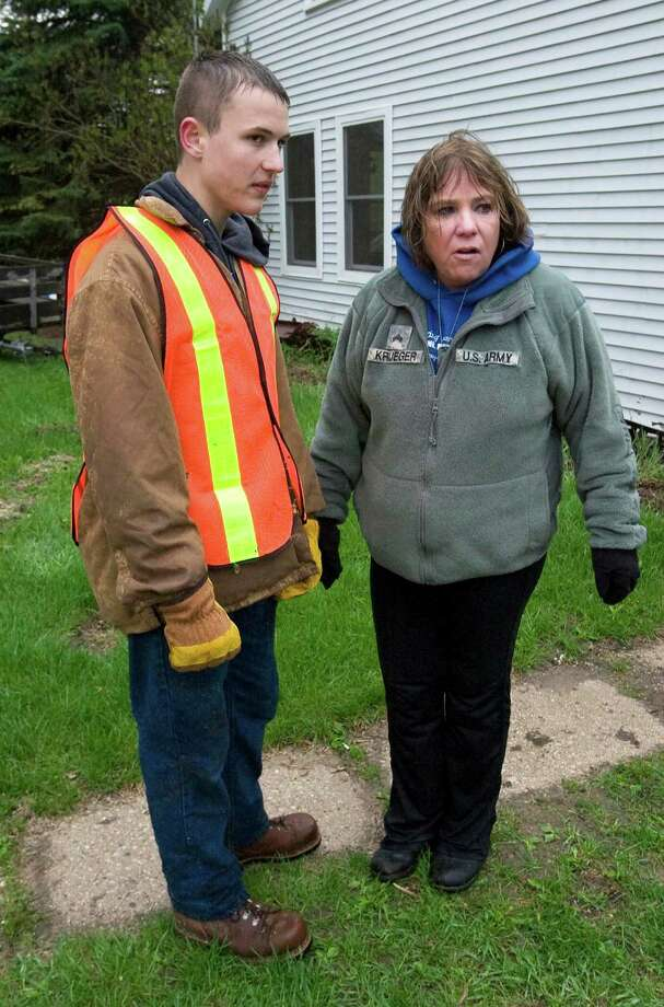 Jeri Krueger, seen here outside her home in Kiel, Wis., with Naval Sea Cadet Tyler Tuttle, lost her daughter, Staff Sgt. Amy Krueger, in the Nov. 5, 2009, attack at Fort Hood. The grieving mother said she shed tears of relief after the man responsible was sentenced to death. Photo: Bruce Halmo, MBO / SHEBOYGAN PRESS