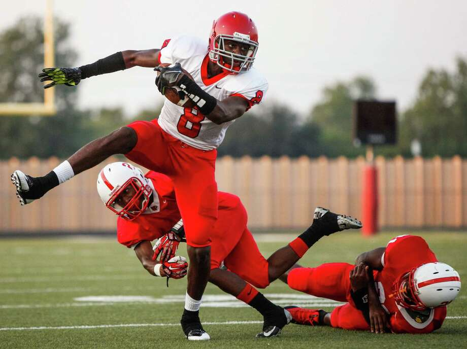 Alief Taylor 22, Bellaire, 9  Alief-Taylor wide receiver Keenen Brown (8) breaks a tackle during the first quarter of a high school football game at Butler Stadium on Friday, Aug. 30, 2013, in Houston, Texas. Photo: Andrew Richardson, For The Chronicle / © 2013 Andrew Richardson