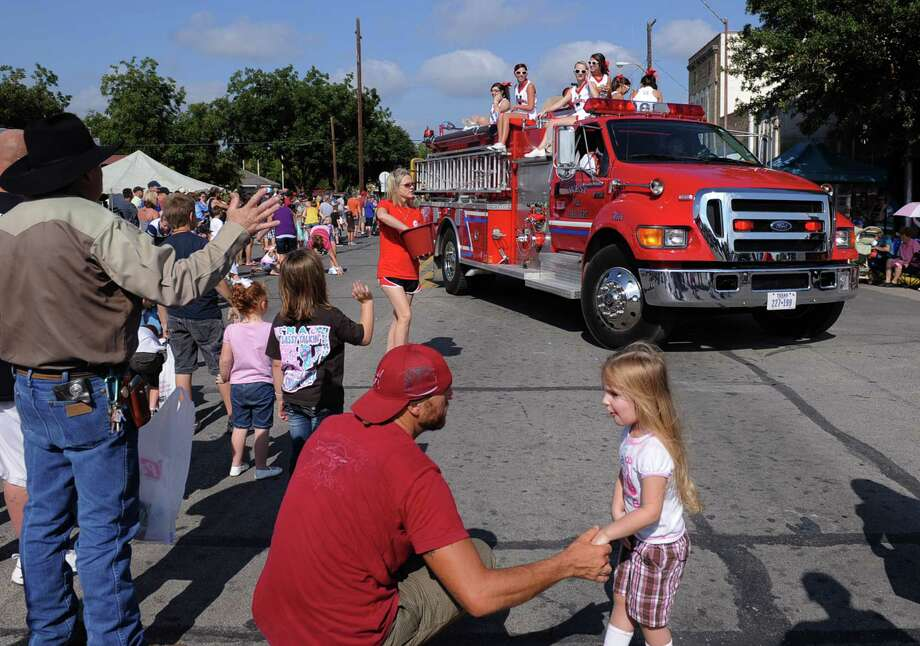 In this Sept. 1, 2012 photo, a volunteer fire department truck turns the corner during the annual Westfest parade in West, Texas. Starting Friday, Aug. 30, 2013, the town will hold the signature celebration of its Czech heritage - the first Westfest since a deadly fertilizer plant explosion tore through the small Central Texas community in April 2013. (AP Photo/Waco Tribune Herald, Rod Aydelotte) Photo: Rod Aydelotte, MBO / Waco Tribune Herald