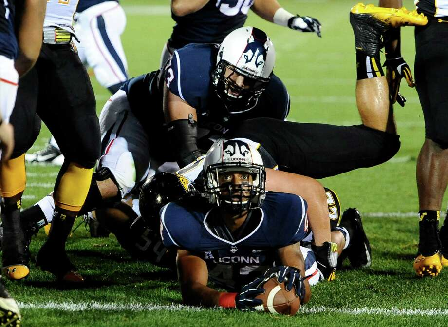 Connecticut running back Lyle McCombs, bottom, looks up to an official at the goal line during the first half of an NCAA college football game against Towson at Rentschler Field in East Hartford, Conn., Thursday, Aug. 29, 2013. McCombs ran for a gain of 22 yards to the 1 yard line. Connecticut failed to score a touchdown on the drive. Photo: Jessica Hill, AP / Associated Press