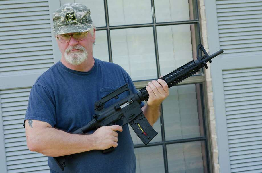 Army retiree Ron Kelly holds his new Mossberg .22-caliber rifle at his Tomball home on Friday. Kelly originally had been denied permission to buy a rifle because of a 1971 marijuana possession conviction. Photo: J.vincephotography, Staff / ©2013 Houston Chronicle