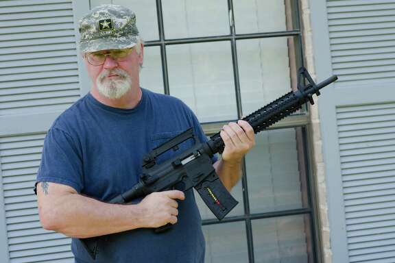 Army retiree Ron Kelly holds his new Mossberg .22-caliber rifle at his Tomball home on Friday. Kelly originally had been denied permission to buy a rifle because of a 1971 marijuana possession conviction.