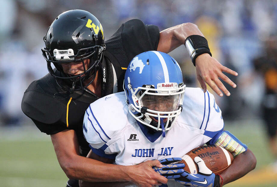 East Central's Austin Allen (43) attempts to wrap up John Jay's Isiah Lloyd (05) during their game at East Central on Friday, Aug. 30, 2013. Photo: Kin Man Hui, San Antonio Express-News / ©2013 San Antonio Express-News