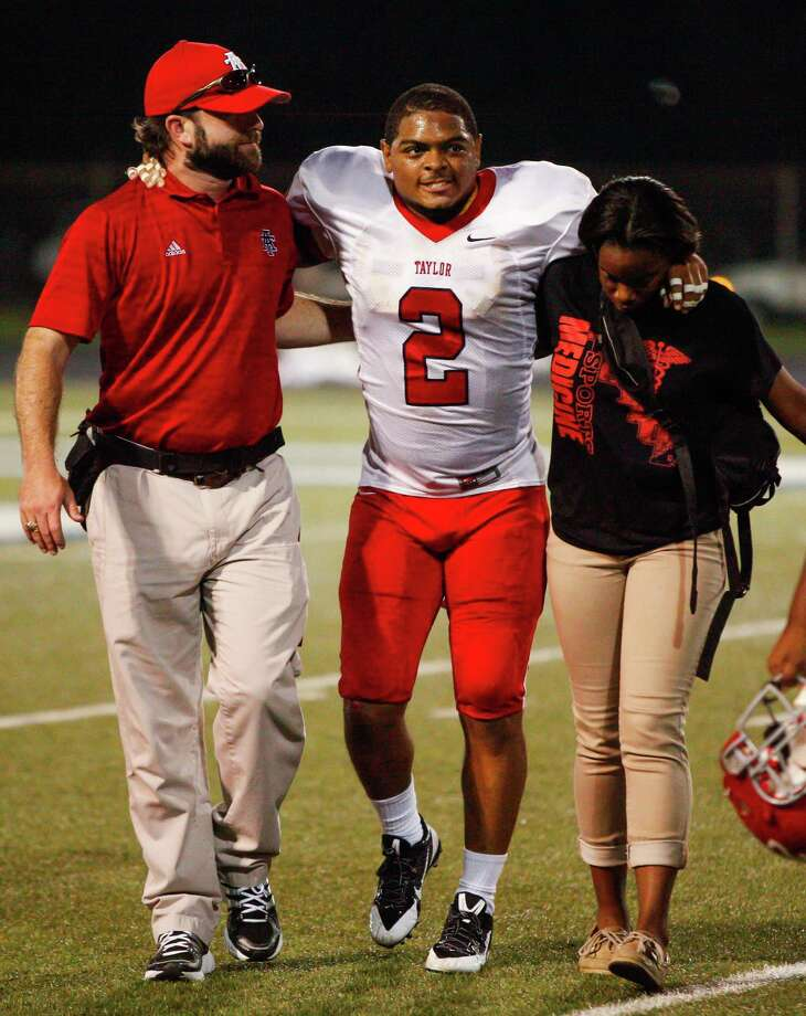 Alief-Taylor defensive lineman Chris Hardeman (2) grimaces in pain as he is helped off the field during the fourth quarter of a high school football game at Butler stadium on Friday, Aug. 30, 2013, in Houston. ( Andrew Richardson / For the Chronicle )  Alief-Taylor defeated Bellaire 22-9. Photo: Andrew Richardson, For The Chronicle / © 2013 Andrew Richardson