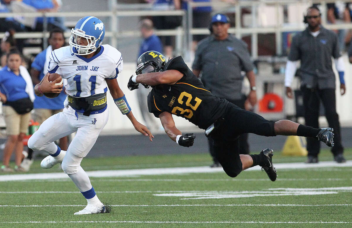 John Jay's Moses Reynolds (11) evades a tackle by East Central's Dennis Chavez (32) during their game at East Central on Friday, Aug. 30, 2013.