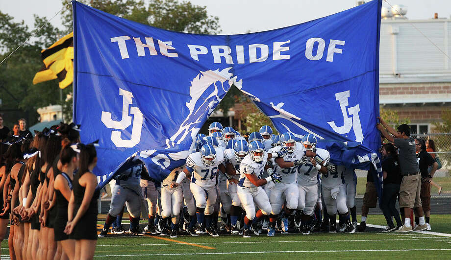 The John Jay Mustangs bust the banner for their football game against East Central at East Central on Friday, Aug. 30, 2013. Photo: Kin Man Hui, San Antonio Express-News / ©2013 San Antonio Express-News