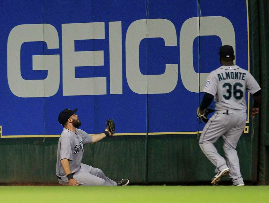 Seattle center fielder Dustin Ackley (13) slides into the bottom of the outfield wall as he catches a fly ball hit by the Astros' Robbie Grossman in the fifth inning. Photo: Karen Warren, Staff / © 2013 Houston Chronicle