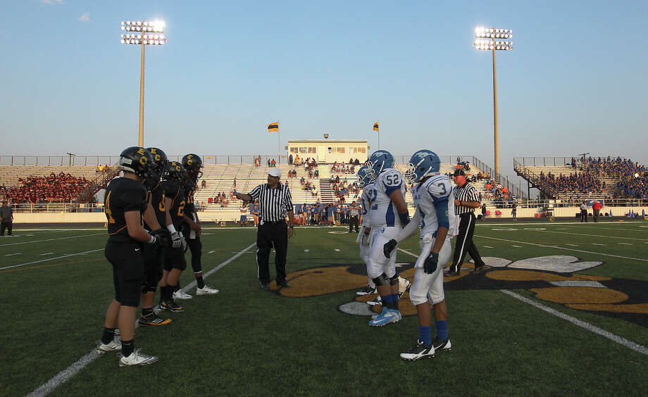 Football players from East Central and John Jay meet near midfield for the start of their 2013 football season at East Central on Friday, Aug. 30, 2013. Photo: Kin Man Hui, San Antonio Express-News / ©2013 San Antonio Express-News