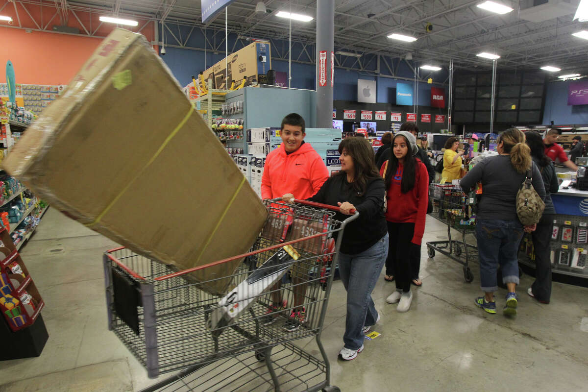 Shopper Eva Avalos pushes a shopping cart out of the electronics area of the H-E-B plus! store at Blanco and Loop 1604 Black Friday November 23, 2012.