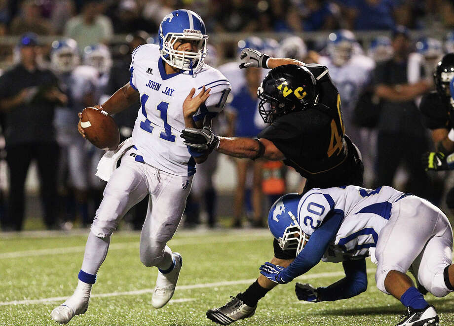 John Jay's Moses Reynolds (11) attempts to run from the grasp of East Central's Mattew Ritch (40) during their game at East Central on Friday, Aug. 30, 2013. Photo: Kin Man Hui, San Antonio Express-News / ©2013 San Antonio Express-News