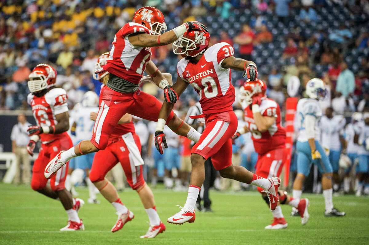 Houston defensive back Earl Foster (30) celebrates with Adrian McDonald (16) after recovering a muffed punt by Southern University for a turnover during the first half of a college football game at Reliant Stadium, Friday, Aug. 30, 2013, in Houston.